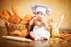 Baby im Koch-Outfit knabbert an Gebäck