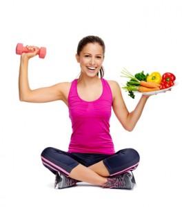 Sportliche Frau mit Hantel und Obstteller