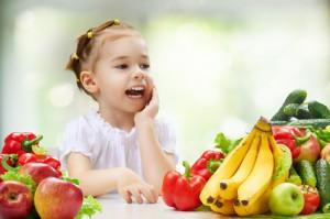 Kleines Mädchen an einem Tisch voller Obst und Gemüse