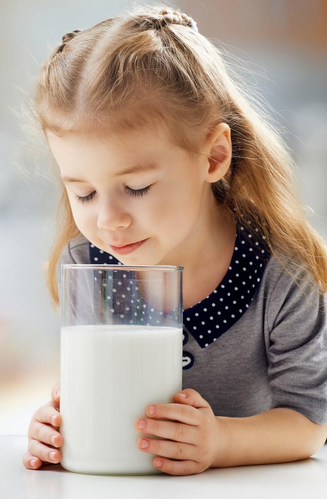 Kleines Mädchen genießt viel Milch