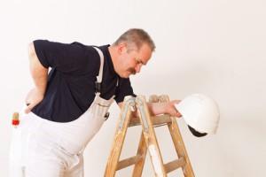 Arbeiter mit Rückenschmerzen stützend an einer Leiter