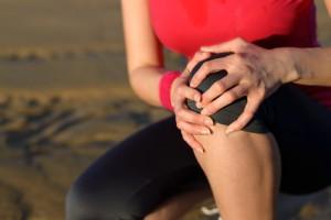 Frau hält sich das Knie wegen einer Kniegelenkarthrose
