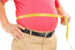 Übergewichtiger Mann mit Maßband um den Bauch
