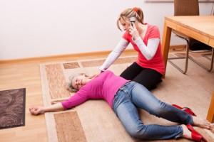 Dame liegt am Boden und Frau hilft