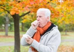 Mann mit Taschentuch beim Husten